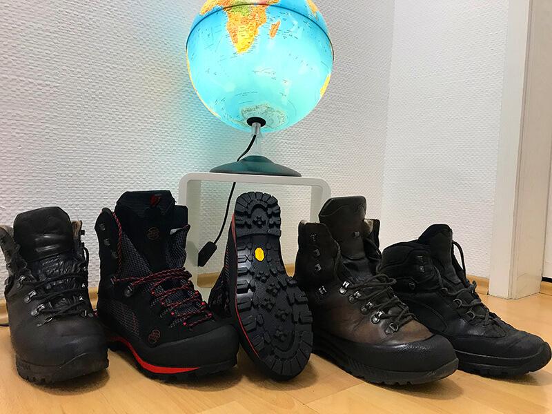 unterschiedliche Bergstiefel mit beleuchtetem Globus