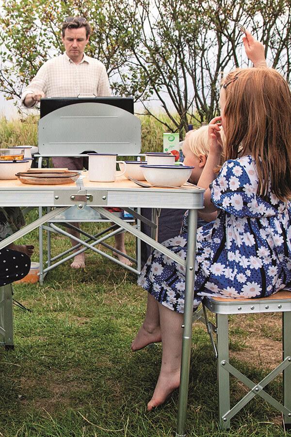 Vater & Kinder beim Grillen auf Campingmöbeln
