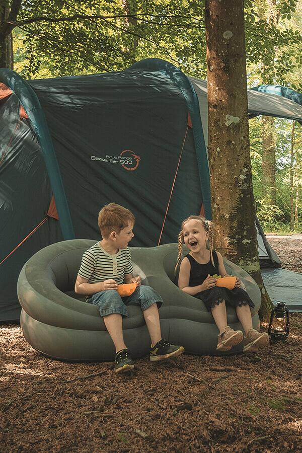 lachende Kinder in aufblasbaren Sesseln vor Zelt